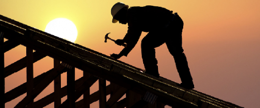 Photo of a roofer working in the sunset