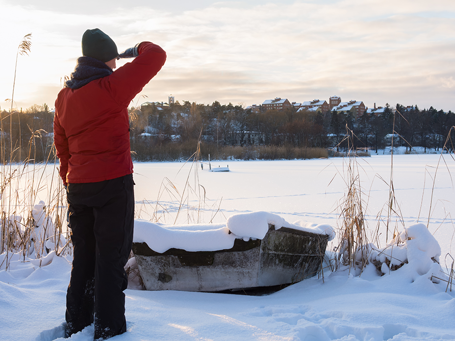 Photo of person standing by frozen lake