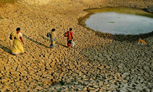Photograph of three women in India walking across an arid landscape to reach a small water source.